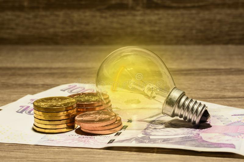 Lit European bulb placed on Czech money royalty free stock photo