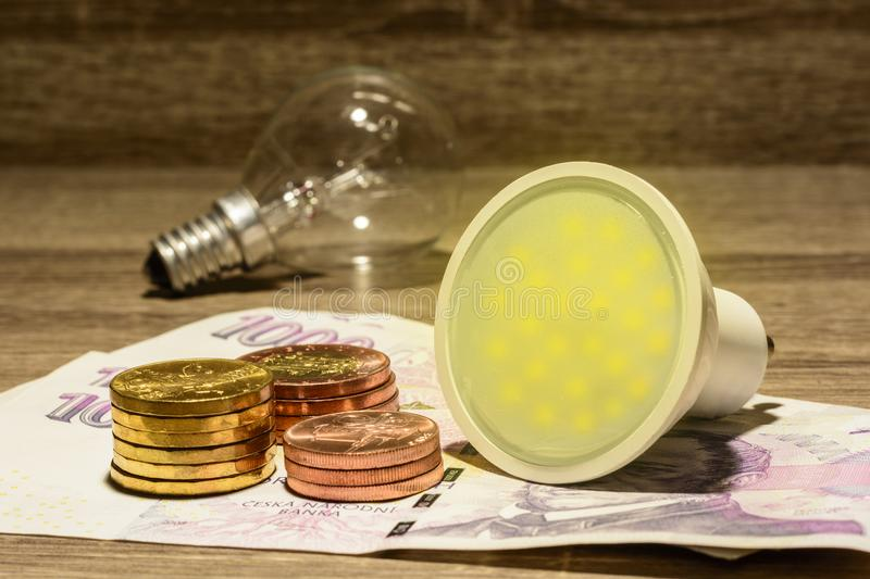 Lit European led bulb placed on Czech money stock images