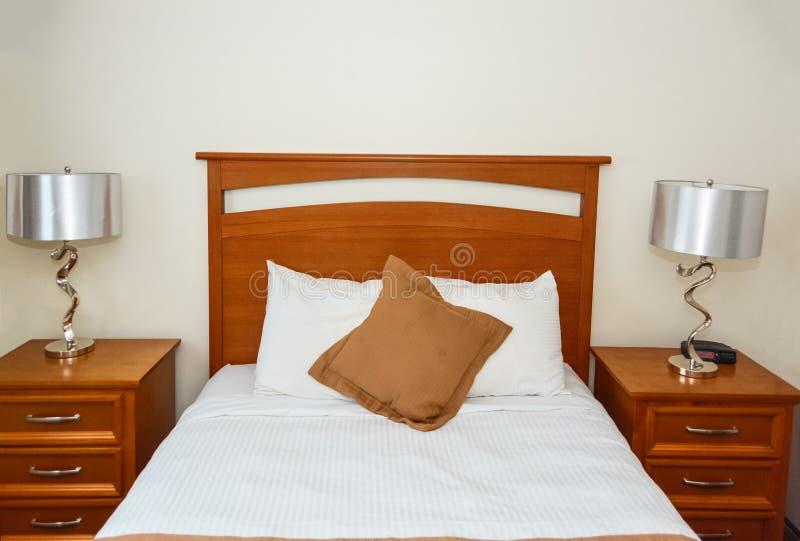 Lit jumeau dans la chambre à coucher avec la lampe sur des tables de chevet photos libres de droits