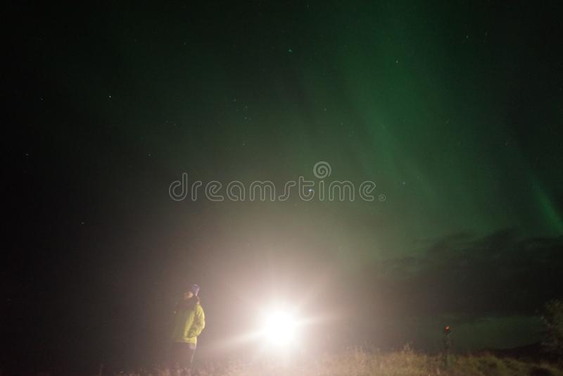 A lit lamp by hikers in a field at night royalty free stock photo