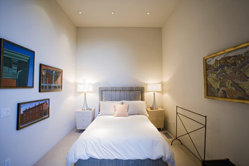 Lit lampen door bed met kaders op muur in slaapkamer stock for Bed in muur