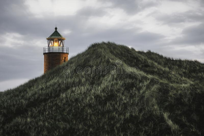 Lit lighthouse on a hill with tall grass and moss on Sylt island. Illuminated orange lighthouse on a high hill with marram grass and moss, on Sylt island, at stock photos
