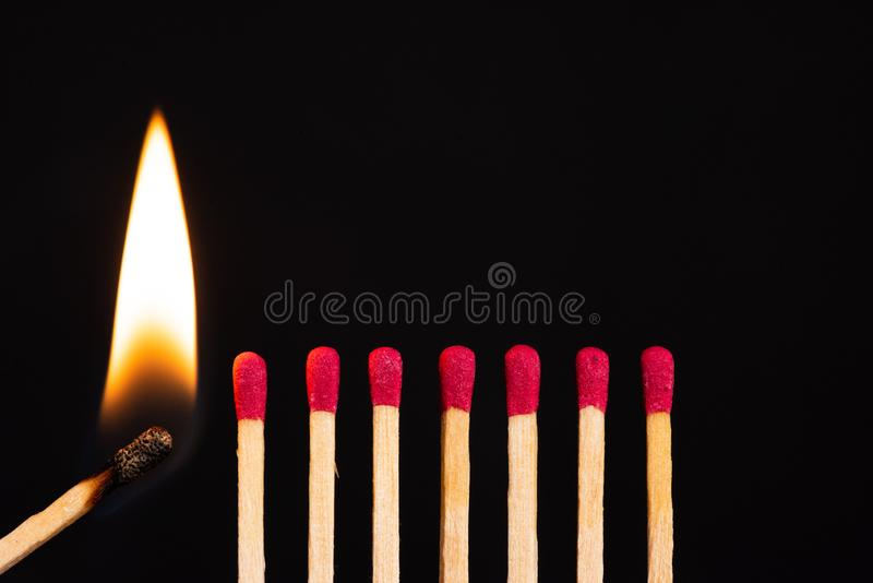 Lit match next to a row of unlit matches. The Passion of One Ignites New Ideas, Change in Others stock photography