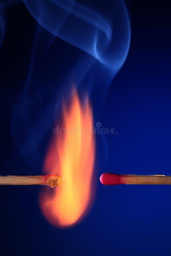 Lit matchstick next to an unlit matchstick stock images