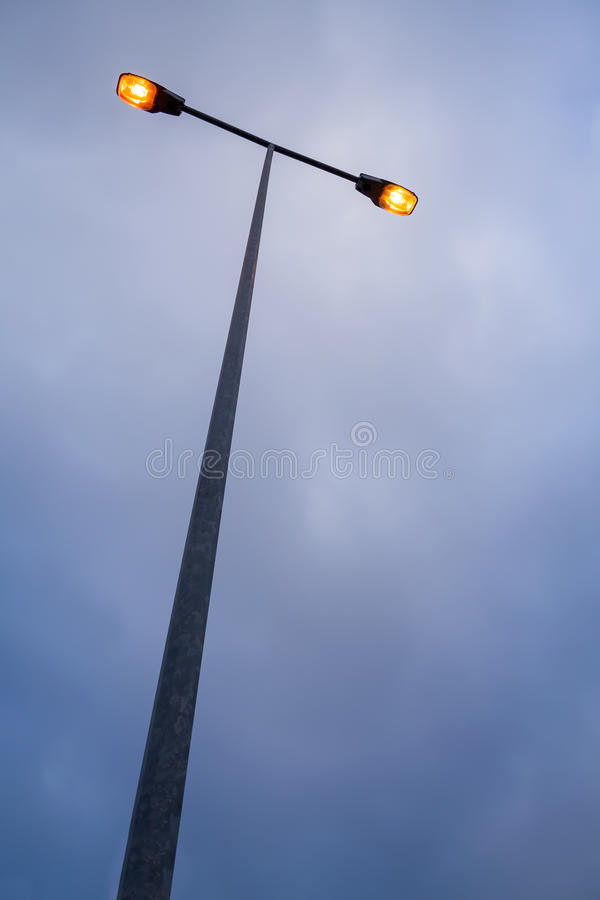 Lit modern streetlamp at evening or early night. With an orange bulb and sky with clouds stock images