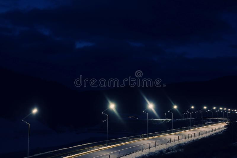 Lit mountain road with snow on sides in evening. Going on winter vacation royalty free stock photos