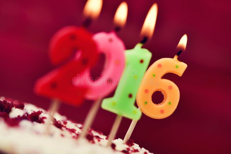 Lit nummer-formade stearinljus som bildar numret 2016 på en kaka royaltyfri fotografi