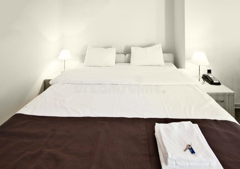 Lit propre et confortable dans la chambre d'hôtel moderne images libres de droits