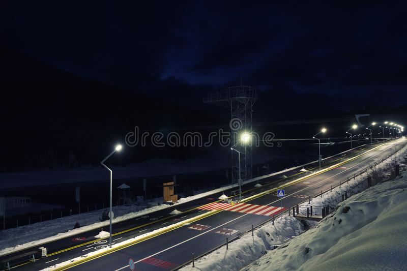 Lit road with snow on sides. In evening stock image