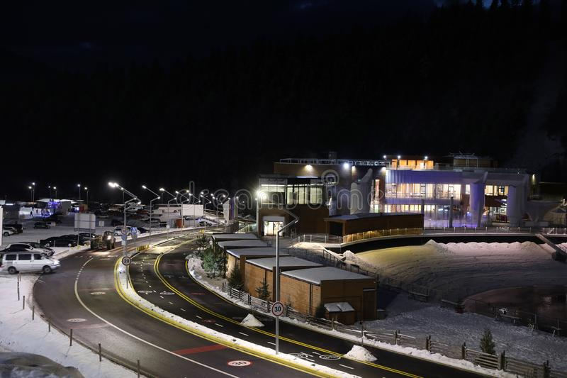 Lit road with snow on sides leading to ski resort. In evening stock photo
