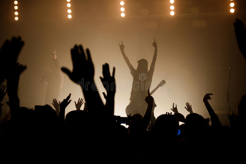 Lit silhouettes of musicians on the smoky stage raising up hand stock photography