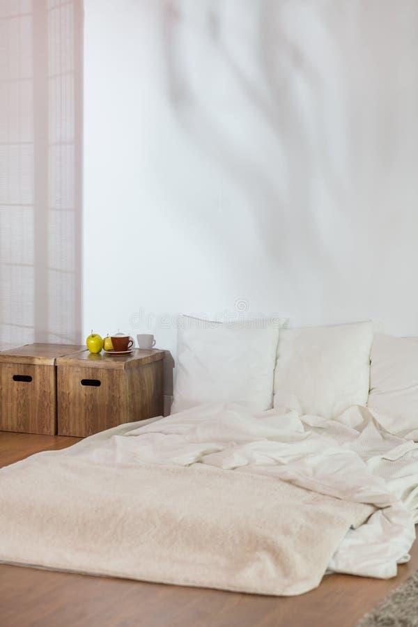 Lit simple dans la chambre à coucher modeste crue image libre de droits