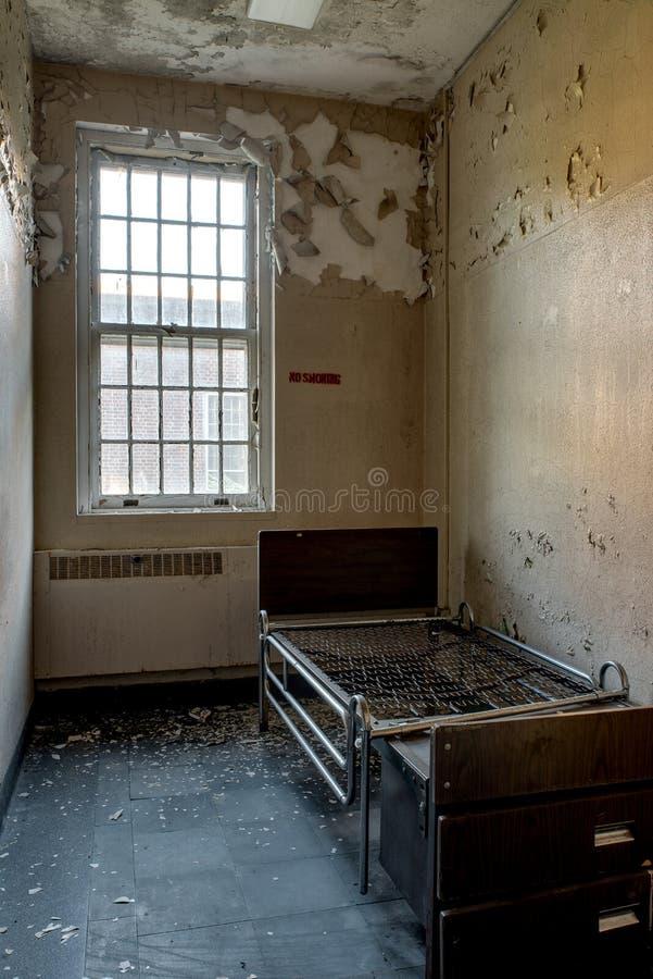 Lit solitaire dans la pièce patiente désolée - hôpital abandonné photos stock