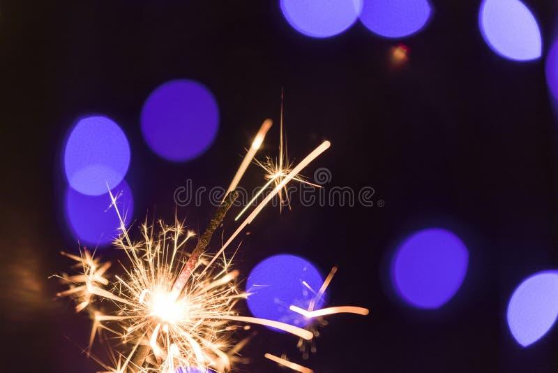 Lit sparkler on the background of flickering garlands. Back stock photo