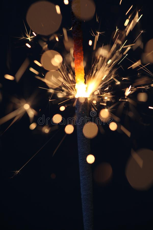 Lit Sparkler on Black Background. Close up of a lit sparkler flickering in yellow against a black ground royalty free stock photography