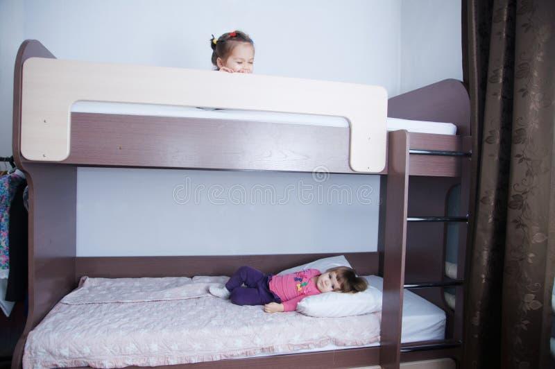 Lit superposé dans la chambre d'enfant petite fille deux jouant sur le lit ombre de chocolat dans l'intérieur avec les murs blanc image libre de droits