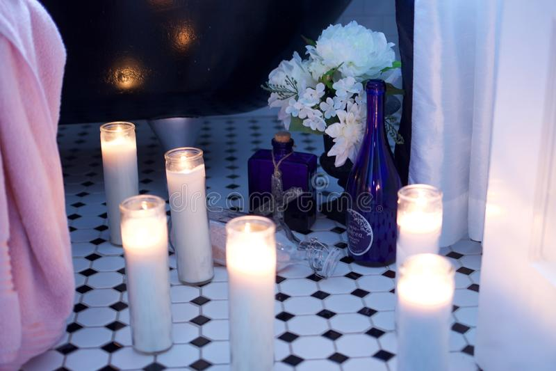 Lit tall glass cylinder candles on octagon title floor next to claw foot tub with flowers. A grouping of tall glass cylinder candles gathered on the octagon tile stock photos