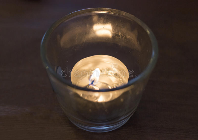 Lit tealight. Candle on a table royalty free stock images