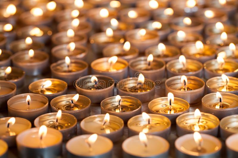 Lit tealight candles close-up. Spread of tea light flames royalty free stock images