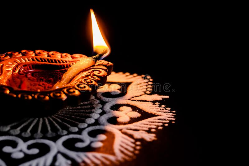 A lit terracotta lamp or clay diya placed on black background. festival of lights or deepawali concept royalty free stock images