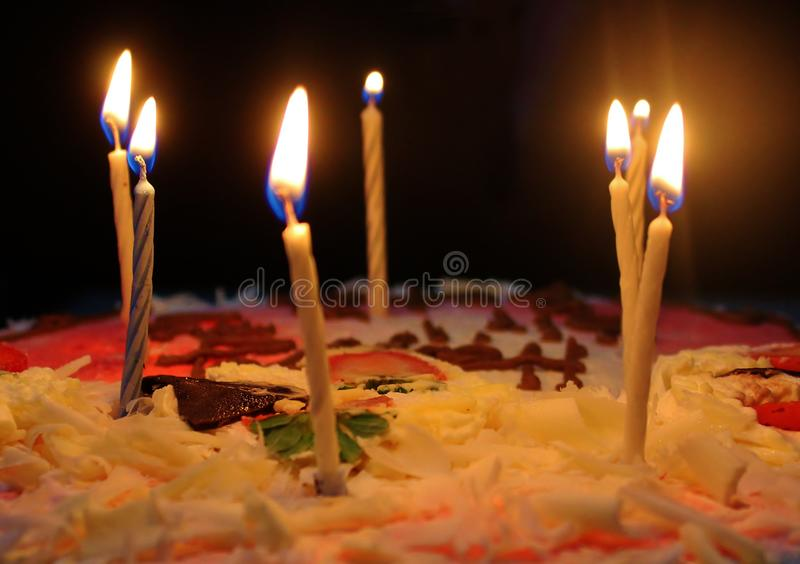 Lit up candles on a birthday cake royalty free stock photography