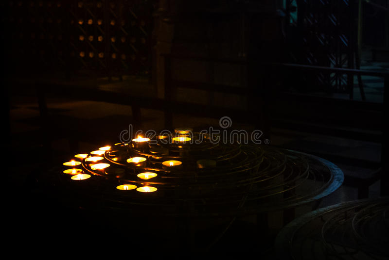 The lit up candles stood by prayers in the darkness of a church room at Notre Dame Cathedral, Paris royalty free stock photos