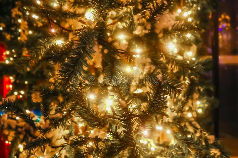 Lit up Christmas tree outside on street with bokeh circle lights on tree and in distance - blurred royalty free stock image