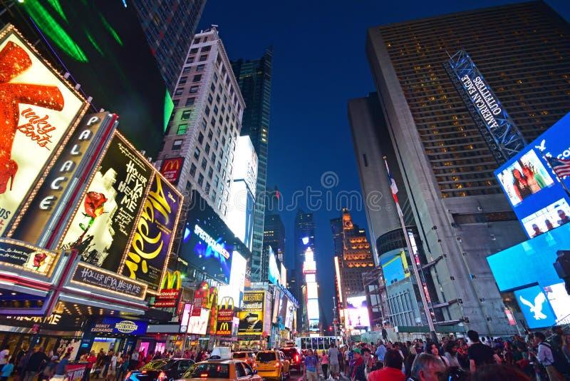 Lit upp New York Time Square i aftonen med trafikblodstockning och den mänskliga folkmassan royaltyfri fotografi