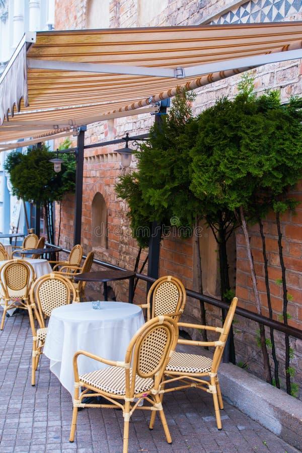 2017-06-25 Litauen, Vilnius, leere Kaffeeterrasse der alten Stadt, Straßencafé in alter Stadt Vilnius mit Tabelle und Stühle lizenzfreie stockfotos