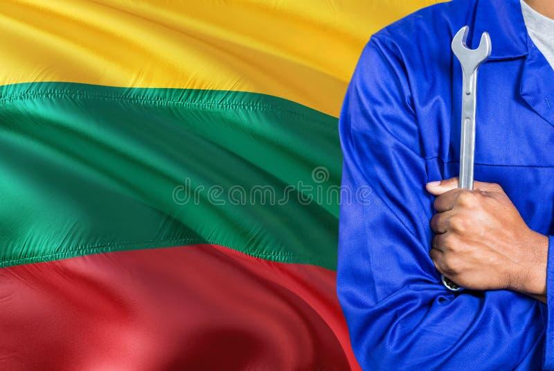 Litauischer Mechaniker in der blauen Uniform hält Schlüssel gegen das Wellenartig bewegen des Litauen-Flaggenhintergrundes Gekreu lizenzfreies stockbild