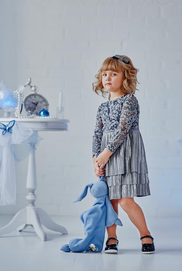 Lite är flickan med en leksak near tappningtabeller royaltyfria foton