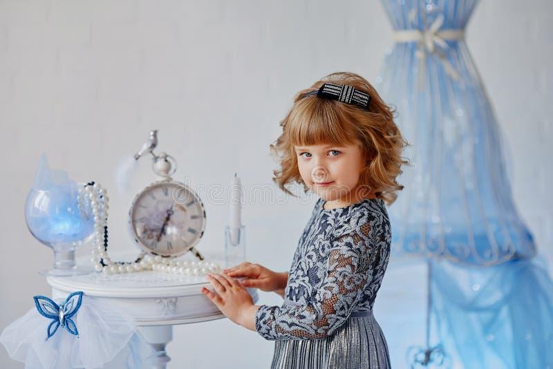 Lite är flickan med en leksak near tappningtabeller arkivfoto
