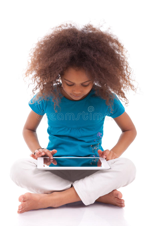 Lite afrikansk asiatisk flicka som använder en tabletPC royaltyfria foton