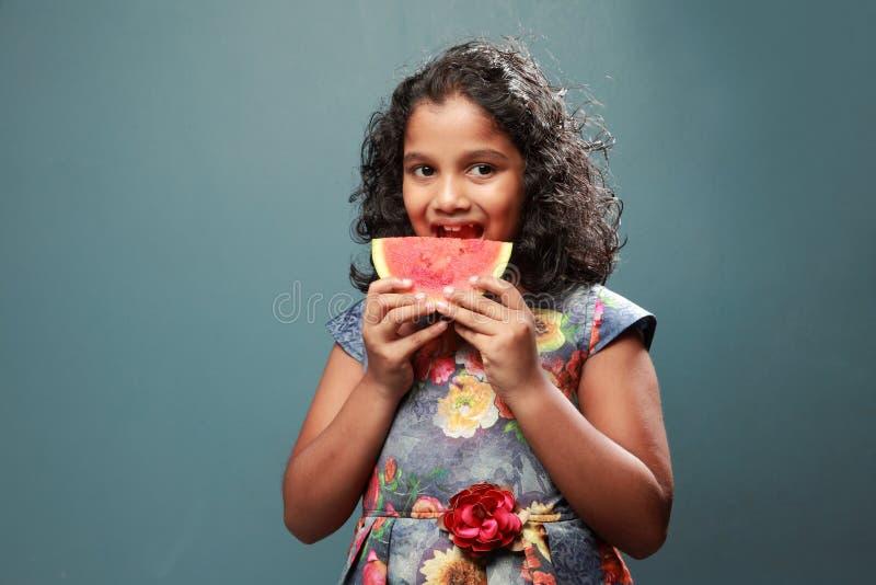 Lite biter flickan en skiva av vattenmelon royaltyfria bilder