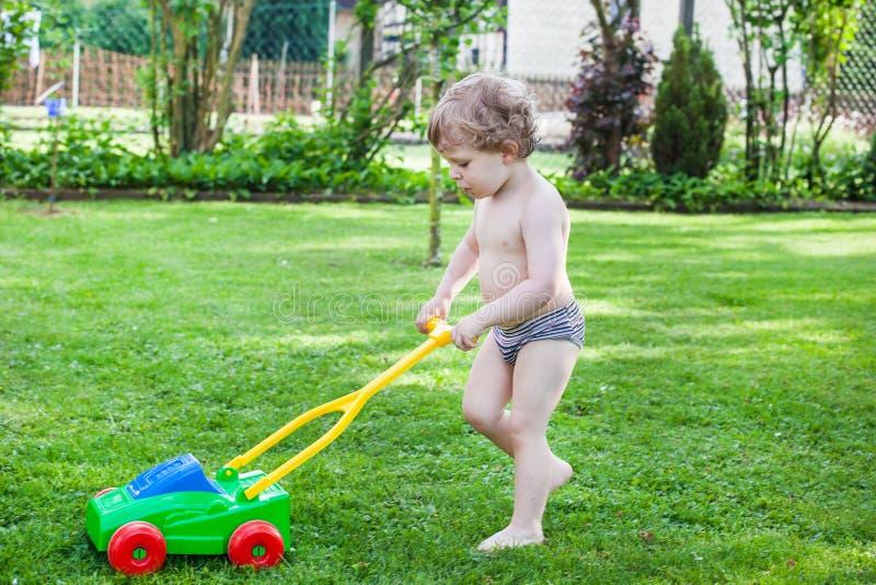 Lite blond litet barnpojke som leker med lawngräsklippningsmaskinen arkivbilder