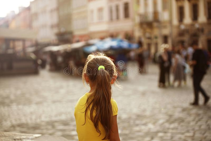Lite blonda blickar för flicka in i avståndsanseendet på gatan av en medeltida europeisk stad little handelsresande Staden centre arkivfoto