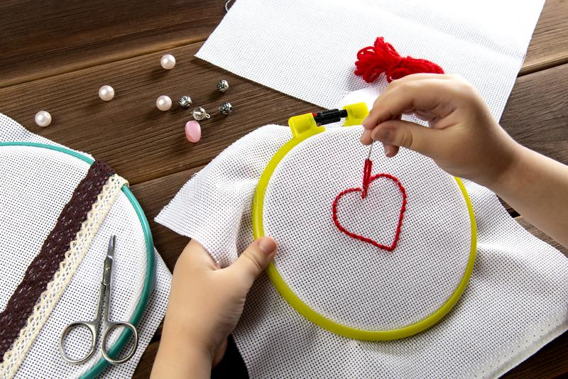 Lite broderar flickan en hjärta på en vit torkdukesikt från ovannämnd tillbehör för broderi på träbakgrund arkivfoton
