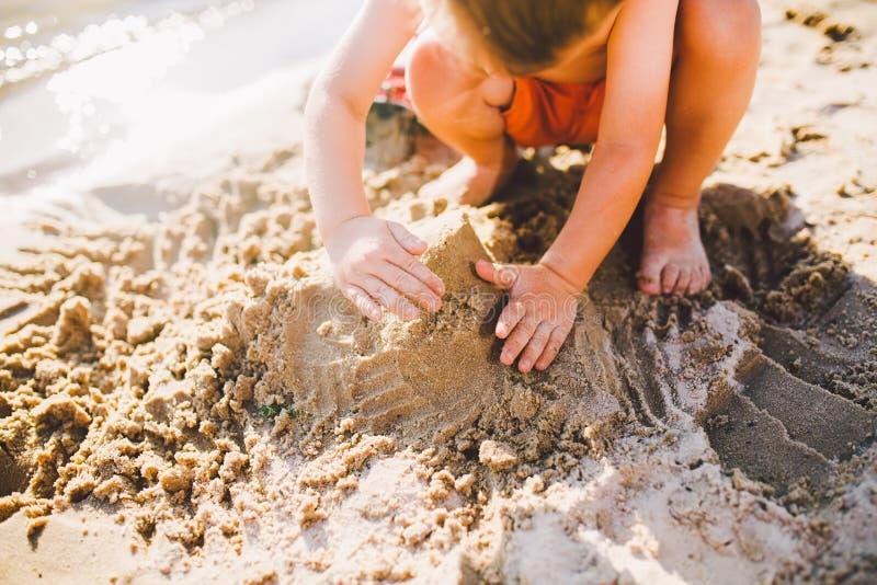 Lite bygger pojken diagram från sanden på kusten av dammet på solnedgången av dagen, händer gräver upp sanden i knaprigt plan royaltyfri fotografi