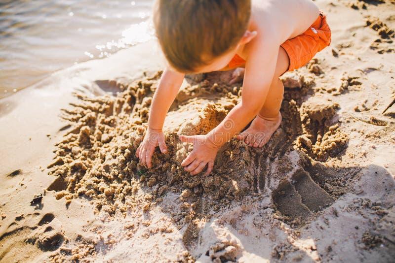 Lite bygger pojken diagram fr?n sanden p? kusten av dammet p? solnedg?ngen av dagen, h?nder gr?ver upp sanden i knaprigt plan royaltyfri foto