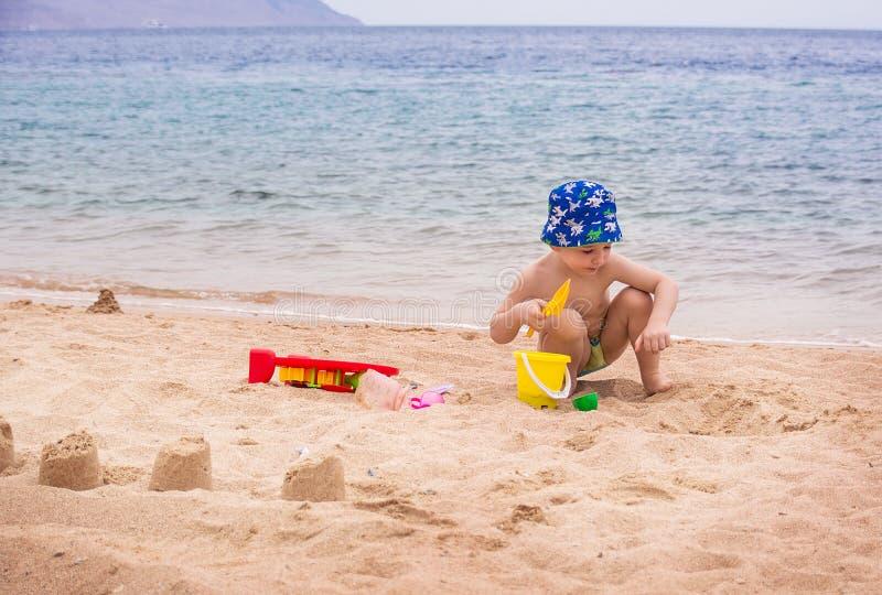 Lite bygger pojken sandslottar på kusten royaltyfri foto