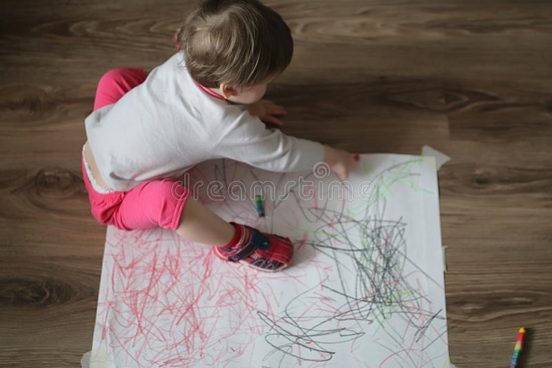 Lite drar flickan med kulöra blyertspennor på ett stort vitt ark arkivfoton