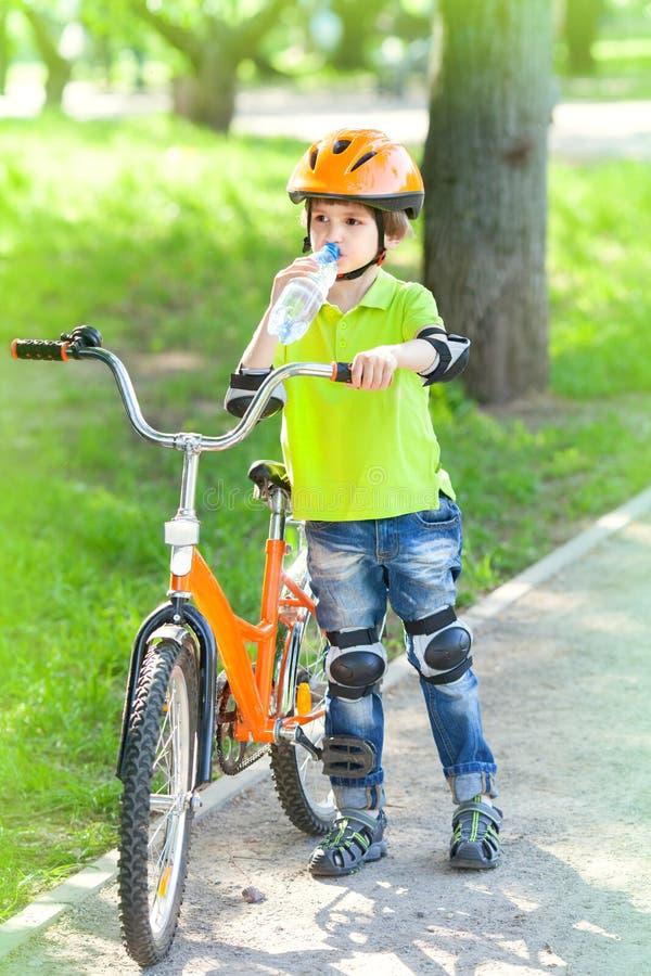 Lite dricker pojken med en cykel vatten royaltyfri fotografi