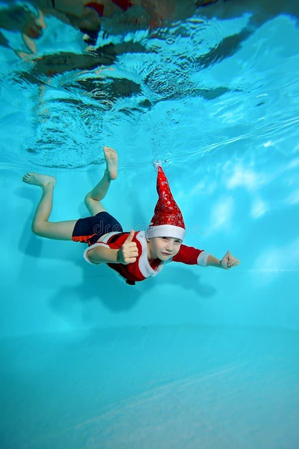 Lite dyker pojken i ett lock och en dräkt av Santa Claus undervattens- på en blå bakgrund och att se kameran Stående skytte arkivbild