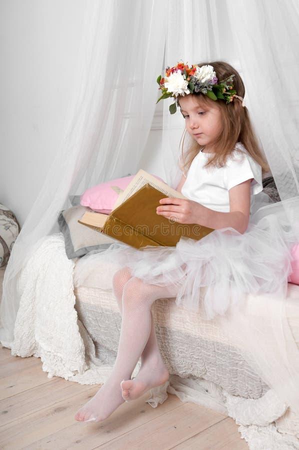 Lite flicka i en balettdansörs fluffiga kjol som sitter på en markissäng och läser arkivbilder