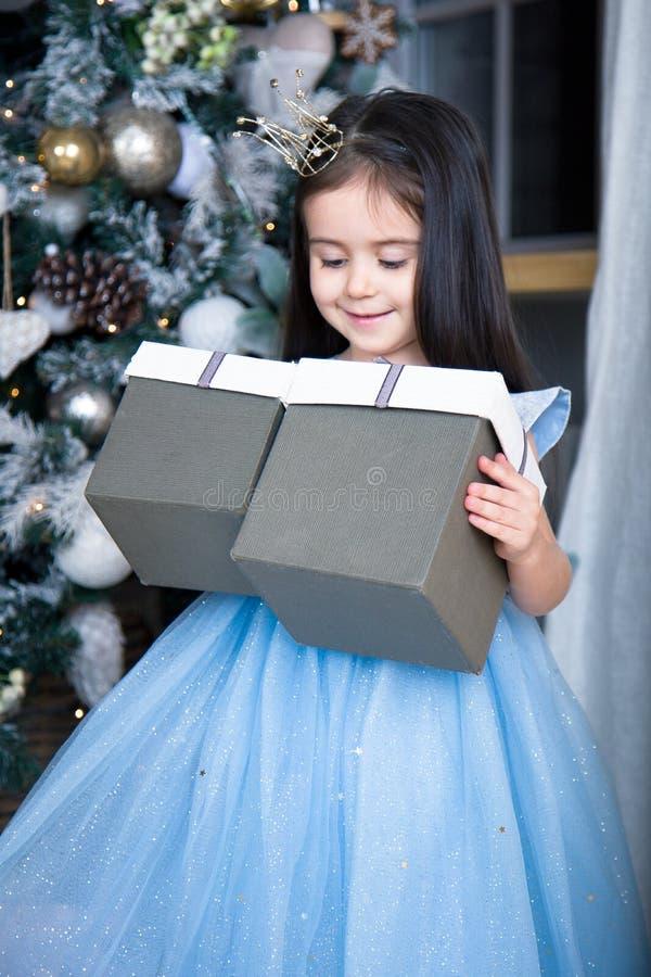 Lite flicka i en härlig blå klänning på julgranen royaltyfria bilder