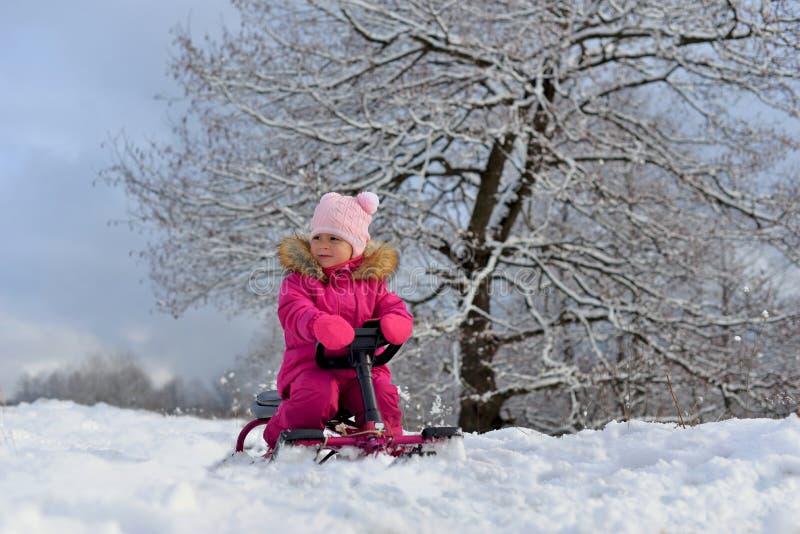 Lite flicka i en rosa färg ner omslaget som sitter på en släde under ett träd i den snöig vintern royaltyfria foton