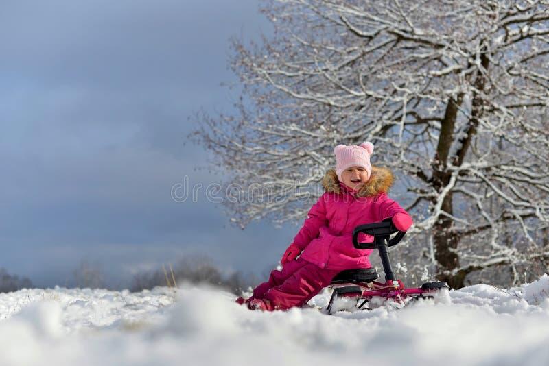Lite flicka i en rosa färg ner omslaget som sitter på en släde under ett träd i den snöig vintern arkivbild