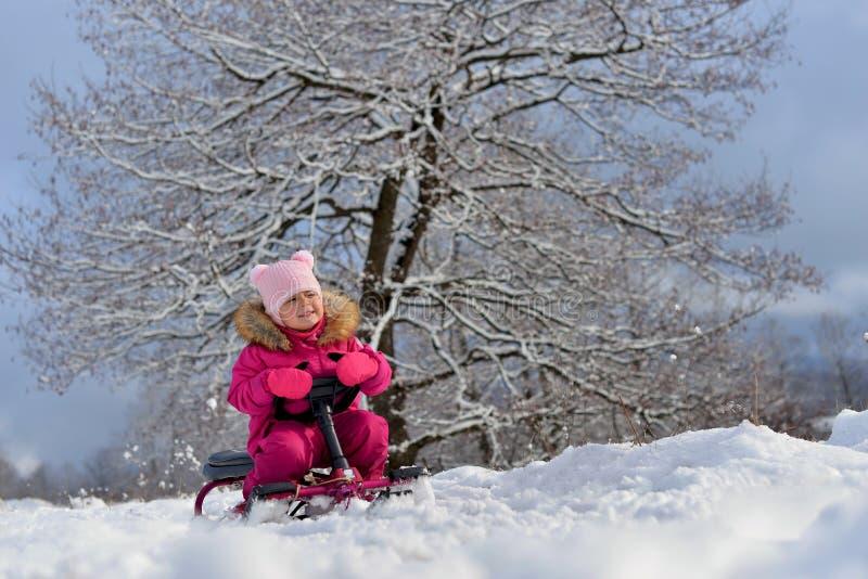 Lite flicka i en rosa färg ner omslaget som sitter på en släde under ett träd i den snöig vintern royaltyfri foto