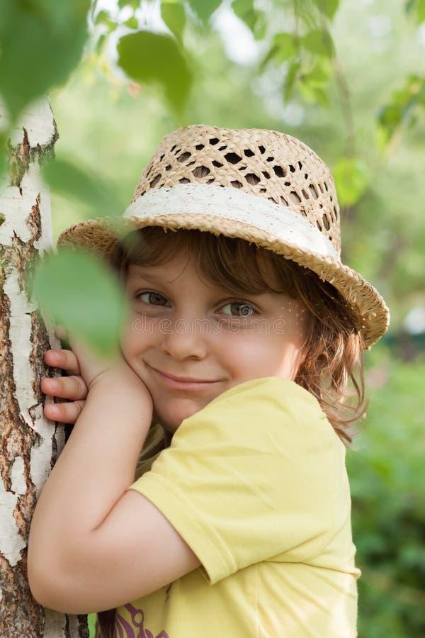 Lite flicka i en sugrörhatt nära björkträdet, sommartidsemester arkivfoto