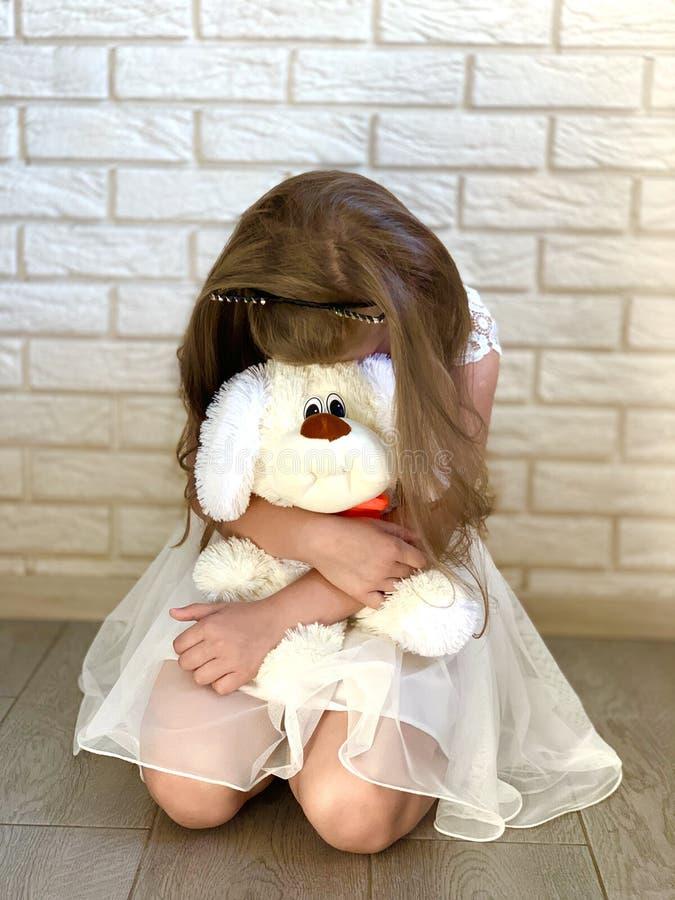 Lite flicka i en vit kl?nning En flicka med en toy royaltyfria bilder